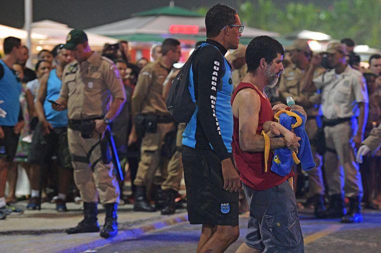 Een gewonde man loopt weg met zijn baby.