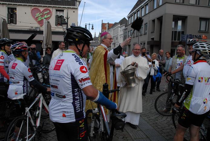Bisschop Gerard de Korte zegende de deelnemers en hun fietsen én een van de twee begeleidersbusjes...