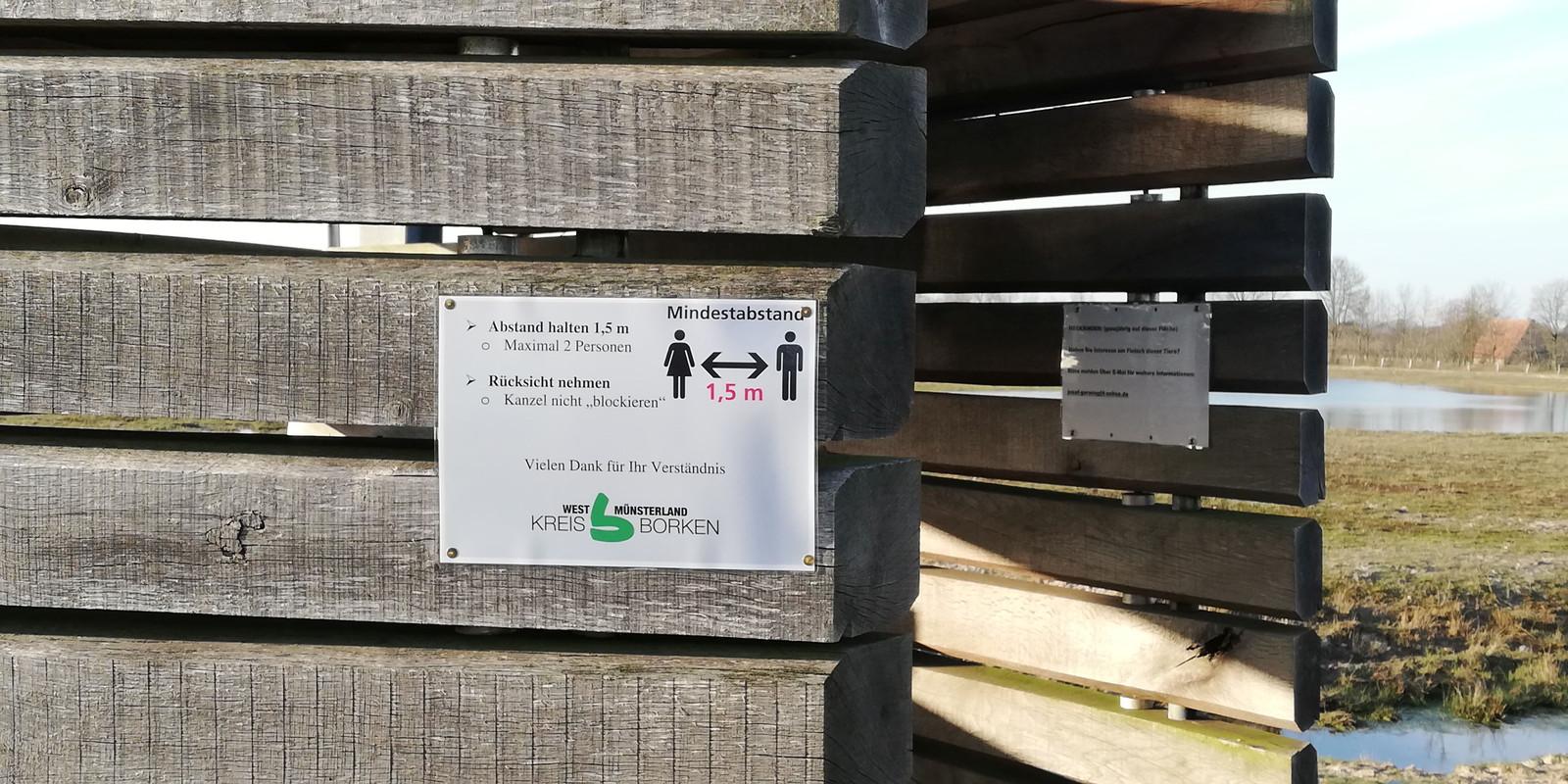 Bij uitkijkpunten in Duitse natuurgebieden vlak over de grens hangen nu borden met informatie over de afstandsregels. @ Kreis Borken