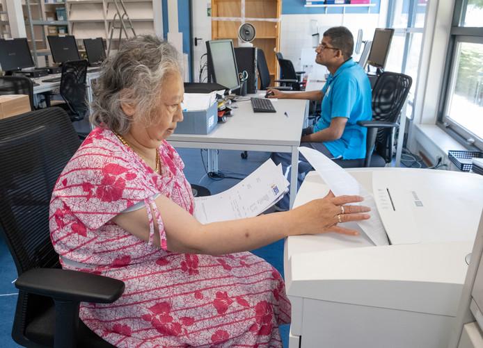 Maudy (voorgrond) stopt papieren in de versnipperaar en Sattish werkt de administratie bij op de computer in de nieuwe werkruimte van KEK Printservice.