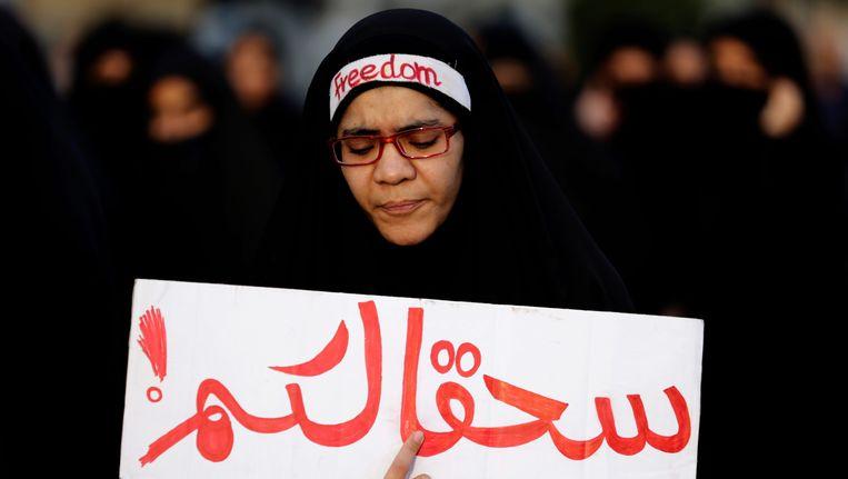 Een anti-overheidsbetoger in Bahrein. Op het bord staat een verwensing, ogenschijnlijk gericht aan de Saudische regering. Beeld AP