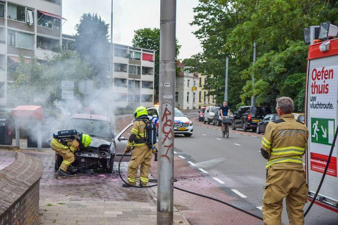 De brandweer blust de autobrand in Arnhem.