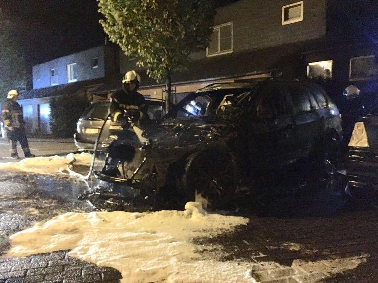 Brandweermannen blussen de auto, maar die is helemaal vernield.