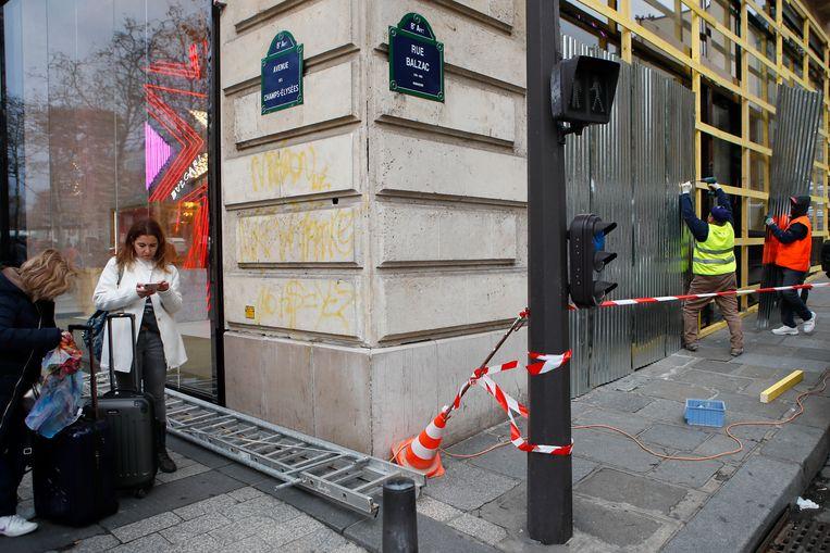 CHAMPS-ÉLYSÉES Werklieden timmeren de etalages dicht van een winkel in het centrum van Parijs. Beeld AP