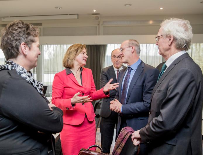 Minister Cora van Nieuwenhuizen op werkbezoek in Deventer in gesprek met burgemeester Hoogendoorn van Oldebroek. Op de voorgrond de wethouders van Deventer en Zutphen.