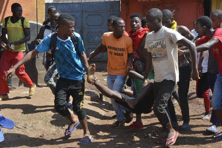 Omstanders dragen een gewonde protestant weg.  Beeld null