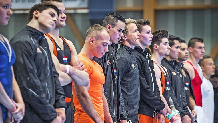 De Nederlandse turners herdenken voor de kwalificatiewedstrijden in Heerenveen de overleden bondscoach Mitch Fenner. Beeld Guus Dubbelman / de Volkskrant