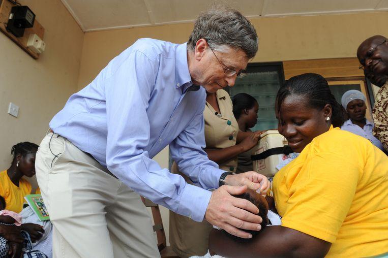 Bill Gates geeft een baby in Ghana een vaccinatieprik tegen het rotavirus, dat diarree veroorzaakt.  Beeld Hollandse Hoogte / AFP