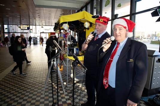 John Peters (rechts) en Jos Biersma zingen kerstliedjes op het station van Nijmegen.
