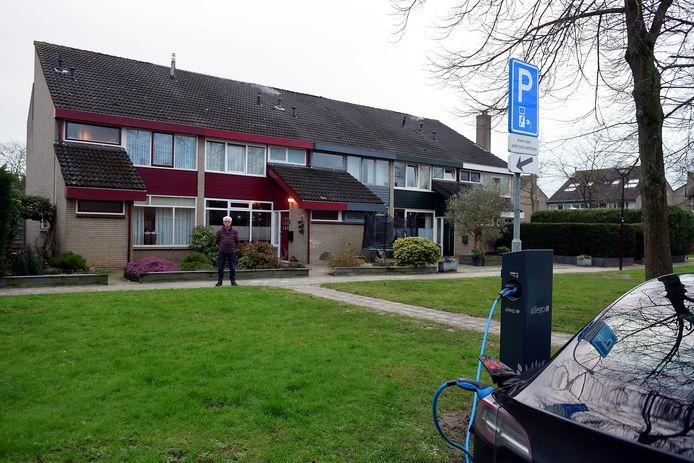 Het laadstation aan Het Laag, op de achtergrond kijkt bewoner Wim van Hees toe.