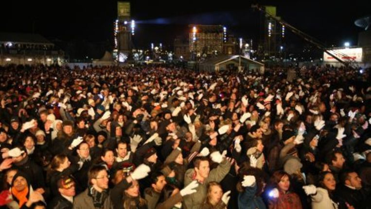 Bezoekers van het Staatsloterij Oud & Nieuwfeest op het Museumplein wuiven uitbundig mee tijdens de optredens. Foto ANP Beeld