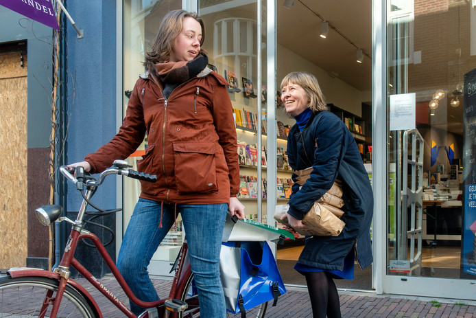 Monique Warnier van boekhandel Hijman Ongerijmd aan de Grote Oord toont een klein deel van de bestellingen bij het damesrijwiel van de zaak terwijl Judith Seiner startklaar staat voor de gratis bezorging binnen Arnhem. Het meeste laten ze bezorgen via de Groene Rijders.