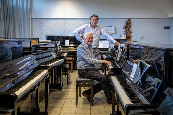 Eigenaar Branny (zittend achter de piano) en zijn zoon Ronald de Graaf in de muziekwinkel in Zwolle. Ze zijn vooral druk met de revisie van piano's en vleugels.