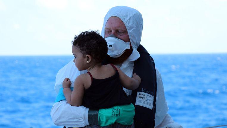 Een bemanningslid van het Nederlandse marinefregat Zr. Ms. Van Amstel brengt een kind aan boord. Beeld anp