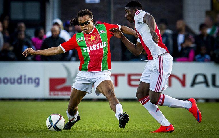 Elton Acolatse (rechts) in duel met Edgar Davids (links) tijdens de benefietwedstrijd tussen Jong Ajax en de Suriprofs op de Toekomst. Beeld anp