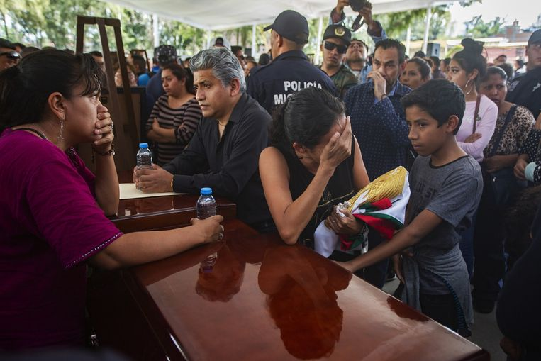 Nabestaanden treuren bij de kisten van dertien politieagenten die afgelopen maandag gedood werden bij een hinderlaag in Aguililla.