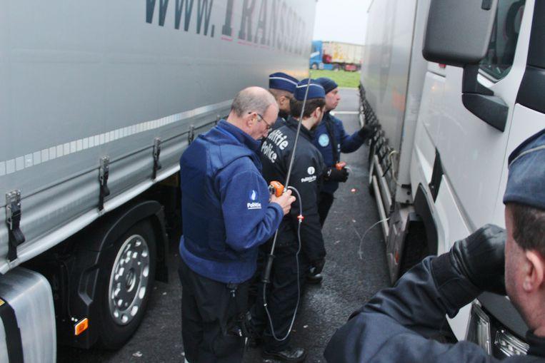 De federale politie doorzoekt vrachtwagens op de snelwegparking in Westkerke. De politiemannen maken gebruik van CO2-meters om te zien of er mensen in laadruimtes zitten.