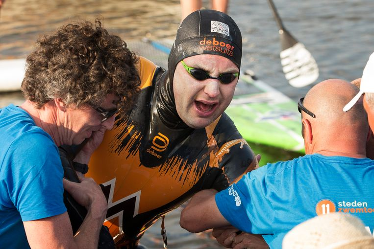 Maarten van der Weijden komt aan bij de finish in Leeuwarden na zijn tweede poging om de Elfstedentocht te zwemmen.
