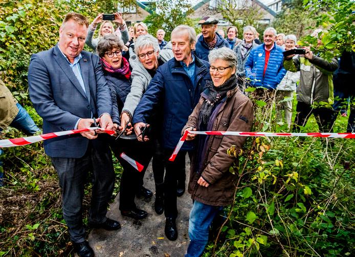 Wethouder van Woudenberg knipt samen met buurtbewoners een lintje door en geeft daarmee het startsein voor de inrichting van de Hennipgaarde in Zevenhuizen.