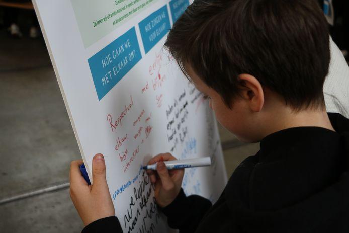 Een scholier schrijft op een bord wat hij belangrijk vindt. De borden worden vrijdag aan de wethouders in de regio gepresenteerd.