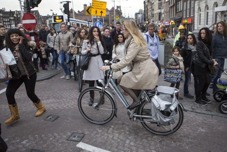 Als in Amsterdam ergens toeristen en fietsers elkaar in de weg zitten dan is het wel hier. Beeld Julius Schrank