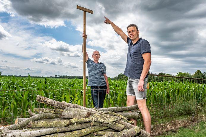 Ad Thomassen (l) en Jeroen Bertens maken bezwaar tegen een zonneweide aan de Oirschotsedijk in Haghorst. Jeroen Bertens wijst op de hoogte van de plaatsen wal rond de zonneweide.