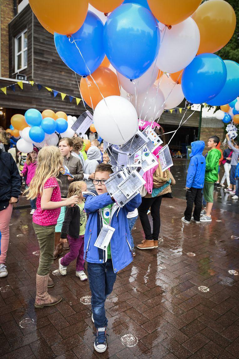 Een jongetje met een twintigtal ballonnen met daaraan een kaartje met de wensen van zijn medeleerlingen.
