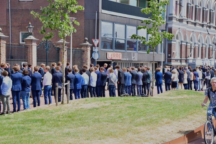 De studenten legden voor de omgekomen surfers Max en Mathijs witte rozen neer voor de sociëteit aan de Phoenixstraat in Delft.