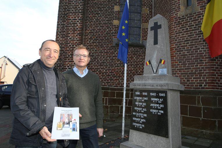 David Swinnen en Eddy Exelmans met hun boek bij het oorlogsmonument van Schoonderbuken.