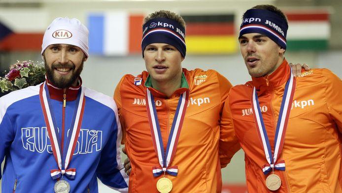 Aleksandr Rumyantsev (L), Sven Kramer en Wouter Olde Heuvel op het podium van de 5000 meter.