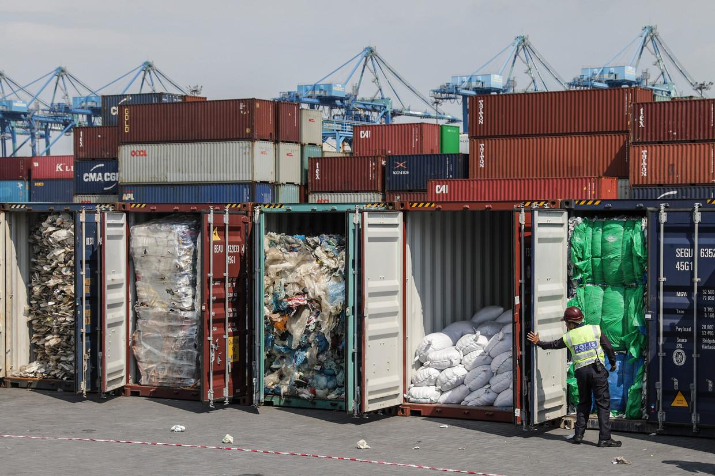 Een Maleisische agent onderzoekt containers vol met plasticafval dat op het punt staat teruggestuurd te worden naar Australië.