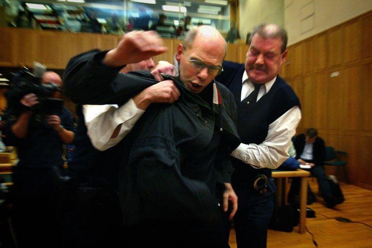 Ernest Louwes verzet zich in 2004 tegen de twaalf jaar celstraf die hij krijgt opgelegd in het gerechtshof in Den Bosch. Beeld ANP / Robin Utrecht