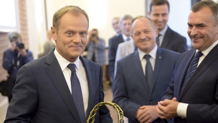 Premier Tusk licht zijn kabinet in over zijn vertrek en krijgt een mandje appels. Beeld Adam Jagielak / Getty