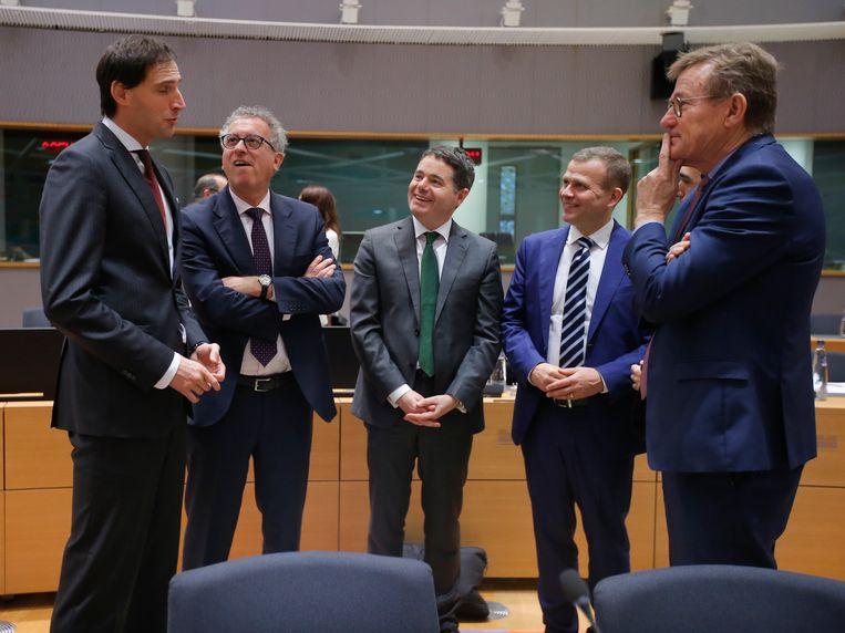 De ministers van Financiën van Luxemburg, Ierland, Finland en België kijken tegen de boomlange Hoekstra op. Beeld EPA