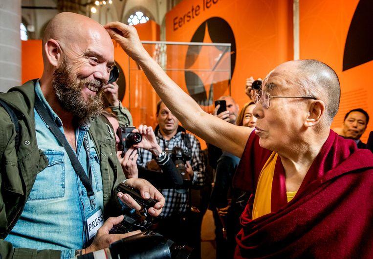De Dalai Lama voelt even aan het hoofd van de fotograaf Beeld ANP