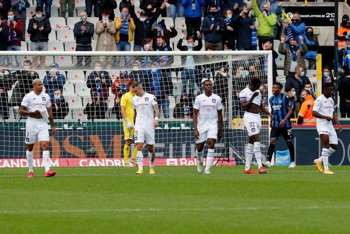 De Anderlecht-spelers druipen ontgoocheld af na de nederlaag op het veld van Club Brugge.