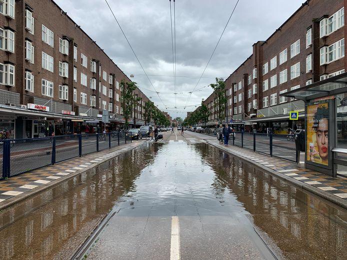 Jan Evertsenstraat. Deze mensen worden zo nat door het opspattende water die de tram gaat veroorzaken.