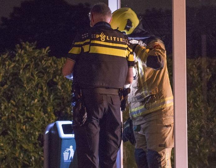 Een agent en brandweerman bij de prullenbak.