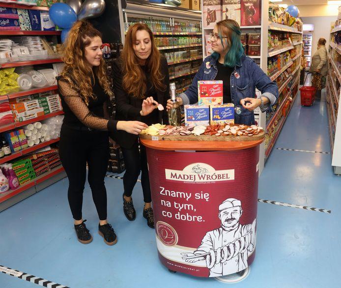 Natalia, Magdalena en Hanna proeven van de Poolse kaas en worst die de klanten krijgen aangeboden.