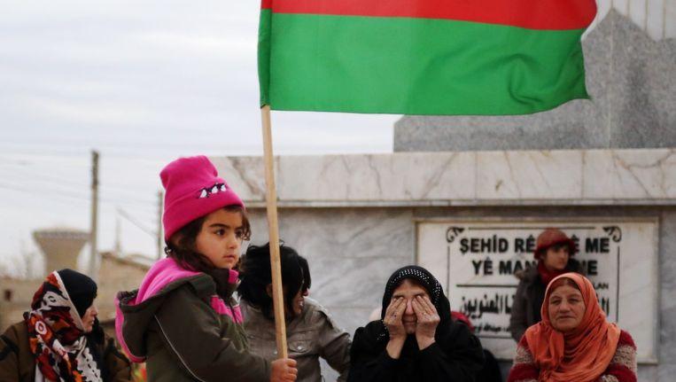 Een Koerdisch meisje met de vlag van de PYD in Qamishlo, de grootste stad van Rojava. Beeld Delil Souleiman / AFP