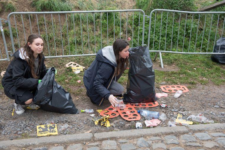 Meisjes van de jeugdbeweging rapen afval op en stoppen het in vuilniszakken.