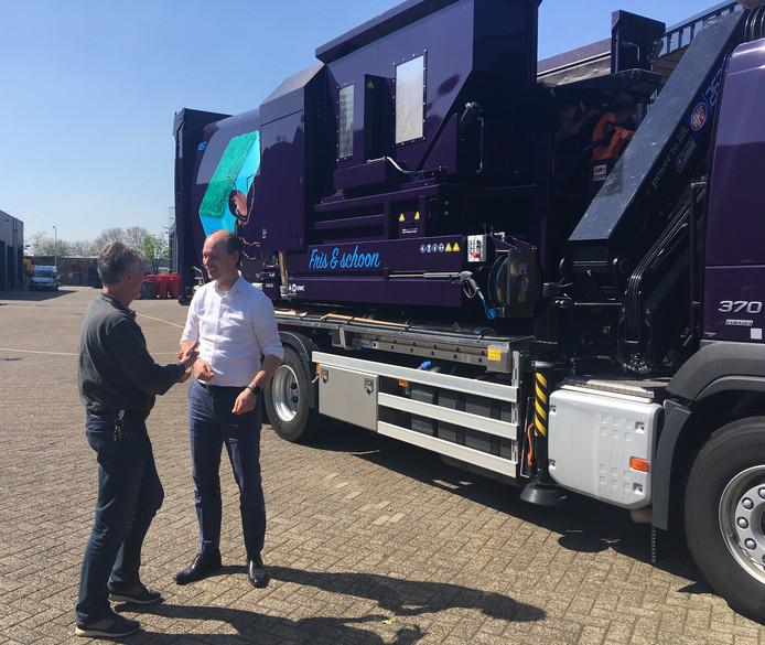 Maarten Plasschaert (l), teamleider bij de gemeentelijke afvalservice, in gesprek met wethouder Daan Quaars bij de nieuwe wagen die de ondergrondse containers schoonmaakt.