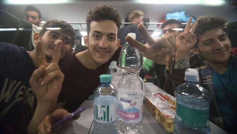 Vluchtelingen in de trein van Wenen naar München. Beeld afp