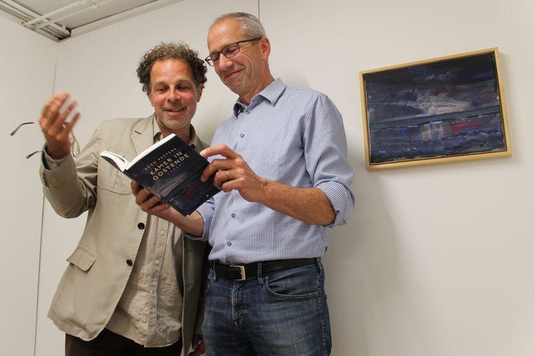 Schilder Koen Broucke (l) en auteur Koen Peeters (r) bij het schilderij van Broucke dat gebruikt is voor het omslag van 'Kamer in Oostende' Beeld Flip Van Doorn