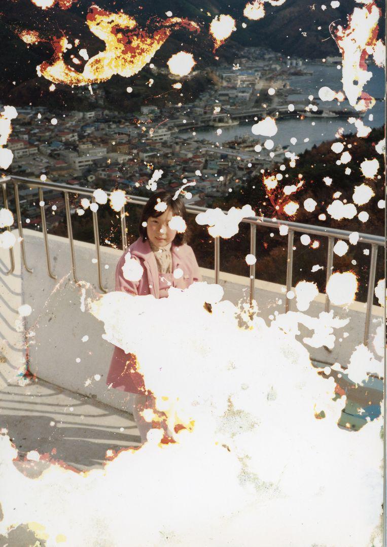 Mayumi, op een van de door het water aangetaste familiefoto's uit de kartonnen doos die ze vond. Beeld uit het boek The Restoration Will van Mayumi Suzuki