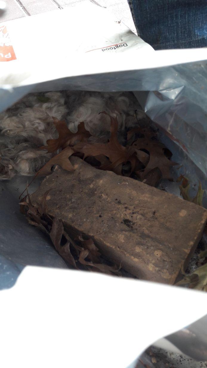 De zak met hondenhaar en een baksteen om 'm op z'n plek te houden.