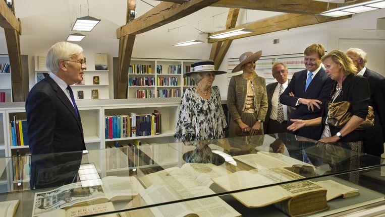 Koningin Beatrix, prinses Maxima en prins Willem-Alexander kijken naar de oude wetsboeken van Nederland die opgeslagen liggen in de bibliotheek van de Raad van State tijdens de opening van het vernieuwde gebouw van de Raad van State in Den Haag. Beeld ANP