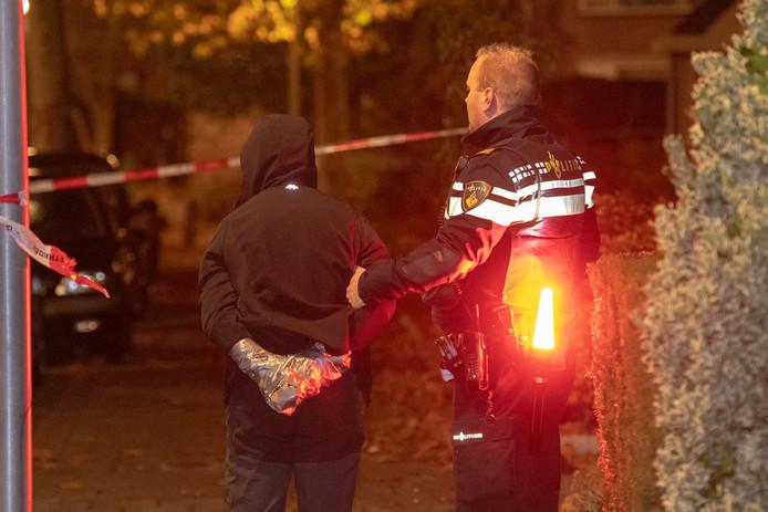 Een verdachte van de plofkraak wordt door een agent weggeleid na zijn aanhouding.
