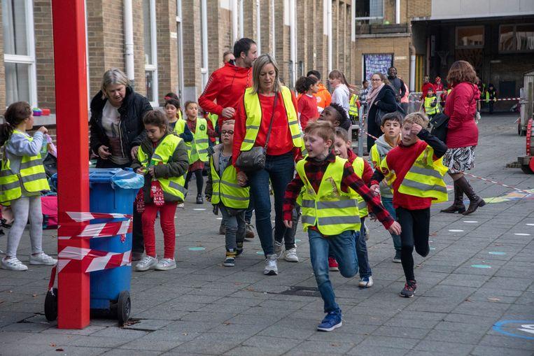 Leerlingen van de Gertrudis basisschool lopen rondjes in en rond de school voor de Rode Neuzen Actie in Wetteren.