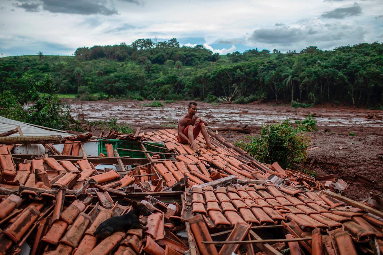 """""""Alles schudde en verdween onder het modder. Ik zag bomen en mensen verdwijnen"""" zegt Emerson dos Santos, 30, terwijl hij op het dak van zijn huis zit."""